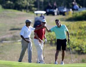 President Barack Obama, left, bumps fists with Cyrus Walker, right, cousin of White House senior adviser Valerie Jarrett, as Glenn Hutchins, center, looks on while golfing at Vineyard Golf Club  (Photo AP/Steven Senne)